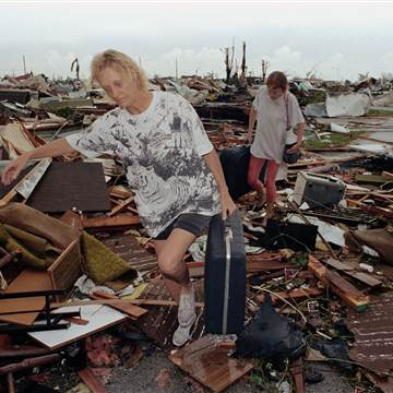 Joan Wallach, left, and daughter, Brenda, leave their trailer park with suitcases they found in the debris. Photo: Lynn Sladky / AP file